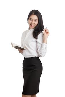 白で隔離のペンとノートを持つ若い幸せなアジアのビジネス女性。