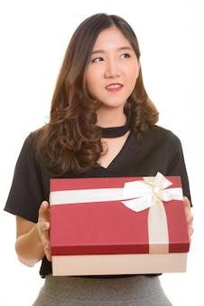 Молодая счастливая азиатская бизнес-леди держит подарочную коробку, думая, готовая к дню святого валентина