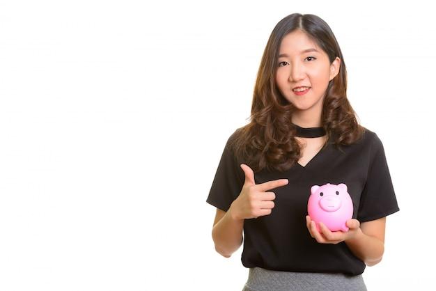 貯金箱を押しながら指を指す若い幸せなアジア女性実業家