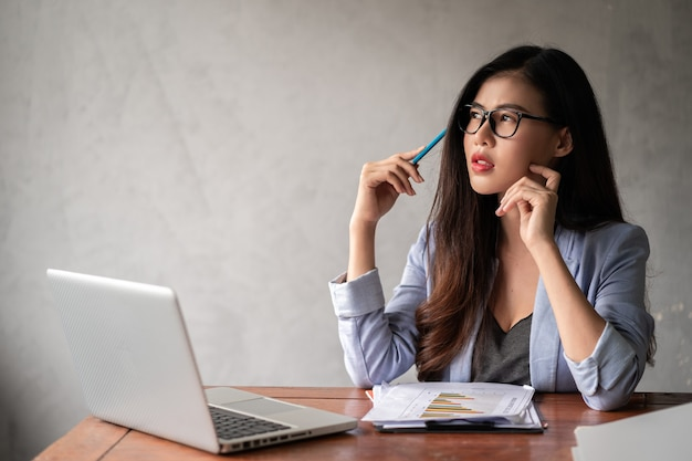 Молодая счастливая азиатская деловая женщина в синей рубашке работает из дома и использует компьютерный ноутбук и думает о своей бизнес-идее