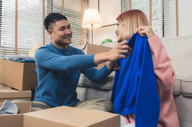 若い幸せなアジア人のカップルは、新しい家に移動し、古い家から古い物をチェックするボックスを開く