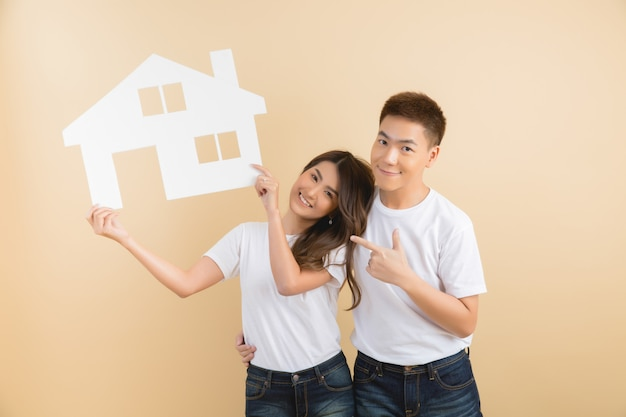 Young happy asian couple presenting the symbols of house