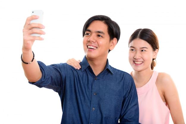 Молодая счастливая азиатская пара улыбается, делая селфи с мобильным телефоном вместе с человеком, фотографирующим
