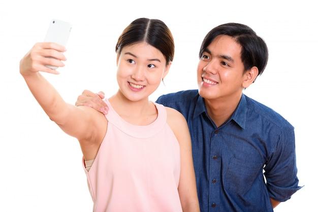 Молодая счастливая азиатская пара улыбается во время селфи с мобильным телефоном вместе с женщиной, фотографирующей