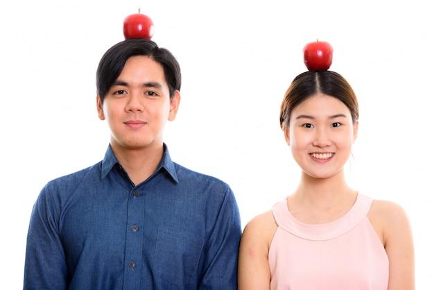一緒に頭の上の赤いリンゴに笑みを浮かべて若い幸せなアジアカップル