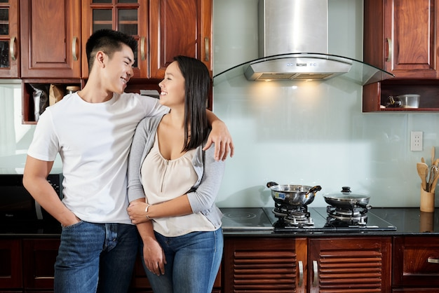 Young happy asian couple standing in kitchen at home, hugging and looking at each other