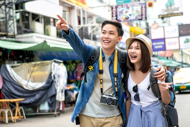 Young happy asian couple tourist backpackers in khao san road bangkok thailand