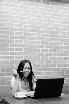 Young happy asian girl smiling while eating froth of the cappuccino with laptop on wooden table on brick wall