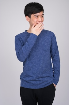 Молодой счастливый азиатский мужчина смеется, прикрывая мо