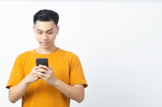 Young happy asian man reading message from smartphone with copyspace on white.