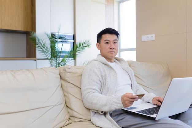 노트북 컴퓨터와 신용 카드를 사용하여 인터넷 상점에서 온라인 쇼핑을 하는 젊은 행복한 아시아 남자