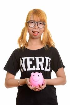 웃 고 돼지 저금통을 들고 젊은 행복 한 아시아 괴상 한 여자