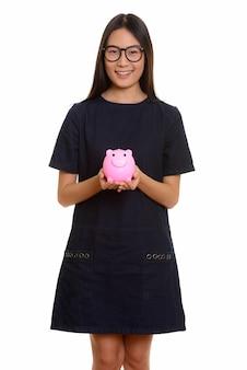 笑顔と貯金箱を保持している若い幸せなアジアの10代の少女