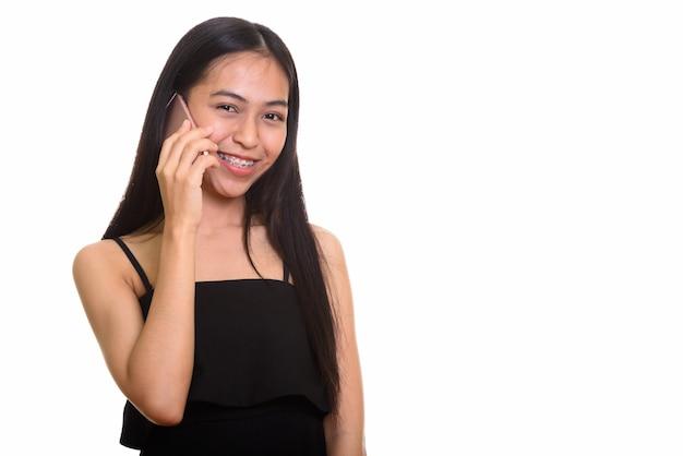 携帯電話で話しながら笑っている若い幸せなアジアの10代の少女