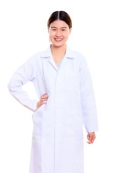 若い幸せなアジア女医笑顔と腰に手で立っています。