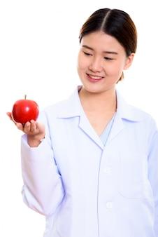 赤いリンゴを押しながら見ながら笑顔若い幸せなアジア女医