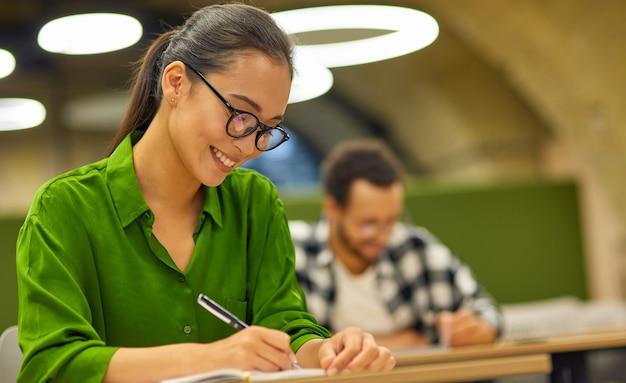 Работник офиса молодой счастливой азиатской женщины женский сидя за столом в офисе или коворкинге