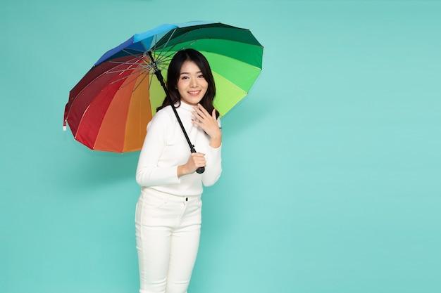녹색 배경에 고립 된 다채로운 우산을 들고 젊은 행복 한 아시아 여자