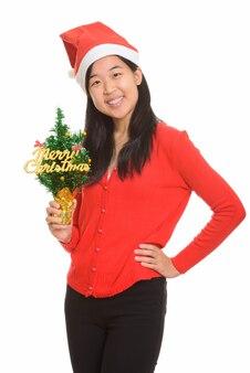 고립 된 크리스마스에 대 한 준비 메리 크리스마스 트리를 들고 젊은 행복 한 아시아 여자