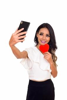 마음을 잡고 전화로 셀카 사진을 찍는 사랑에 젊은 행복 아시아 여자