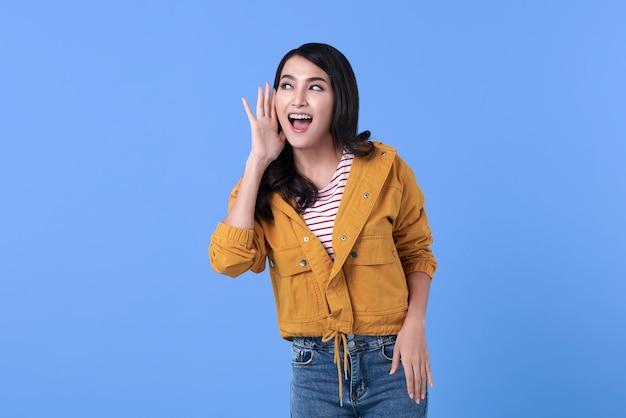 젊은 행복 아시아 여자 블루에 고립 된 그녀의 귀에 이야기 또는 험담을 들어요.