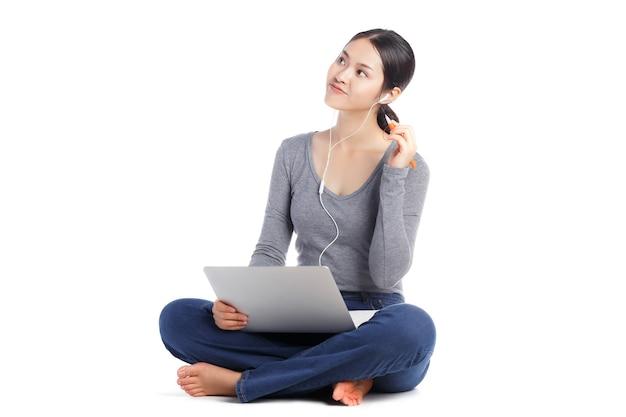 Молодая счастливая азиатская женщина, сидящая на полу с наушниками или светской беседой с портативным компьютером на ее ногах, изолированных на белой стене. привлекательный студент, обучающийся онлайн, хочет скопировать пространство