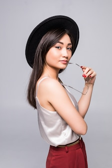 Young happy asian woman smiling in summer hat over white wall