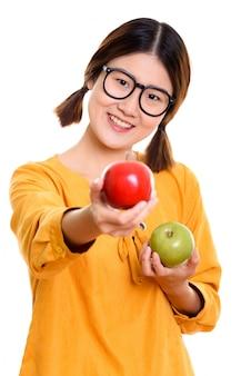 Молодая счастливая азиатская женщина улыбается, держа зеленое яблоко и давая красное яблоко