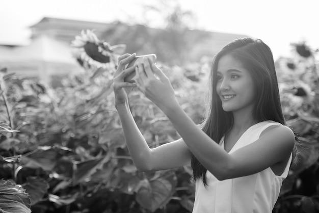 咲くひまわりの畑で携帯電話で自撮り写真を撮りながら微笑む若い幸せなアジア女性