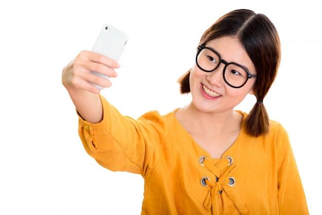 携帯電話でselfie写真を撮りながら笑っている若い幸せなアジア女性
