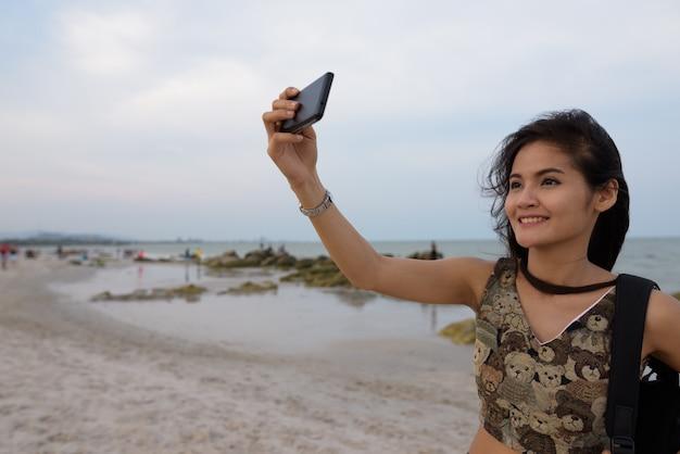 Молодая счастливая азиатская женщина улыбается, снимая селфи