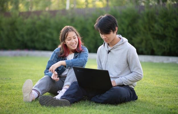 Молодой счастливый азиатский молодой человек и девушка общаются в социальных сетях или в видеочате, сидя на лужайке, выборочный фокус