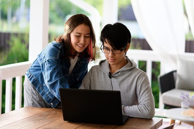 若い幸せなアジアの若い男と女は、ソーシャルネットワーク上で通信するか、選択的な焦点に座ってビデオチャットをしています