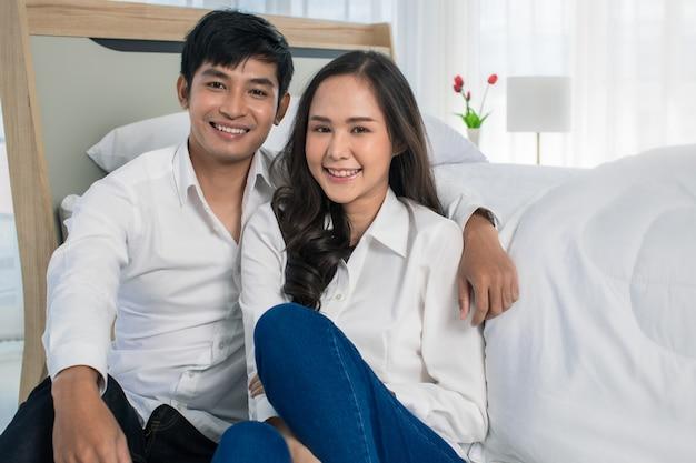 Молодые счастливые привлекательные азиатские пары носили чистую белую рубашку, сидя вместе на полу в спальне, улыбаясь в камеру с белым фоном занавеса. концепция любви и счастливых отношений.