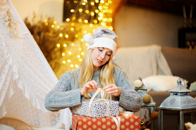 Young happy attractive blonde woman girl wraps paper christmas gift boxes