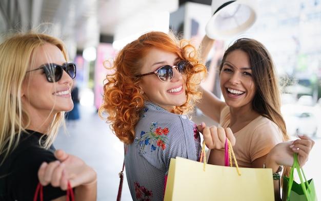 市内の買い物袋を持つ若い幸せな魅力的な女の子。