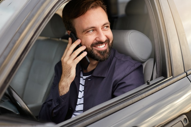 Young happy attractive successful bearded man sits on the car and talking on the phone with his friend, smiling broadly and looking away.