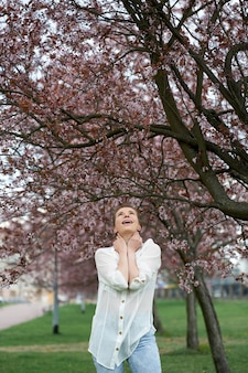 Young happy attractive woman on the background of blooming sakura.