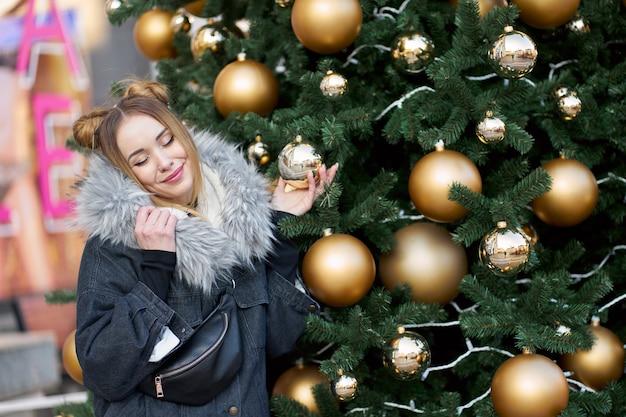 황금 공 및 조명 크리스마스 트리 배경에 포즈 닫힌 된 눈을 가진 젊은 행복 한 매력적인 여자.