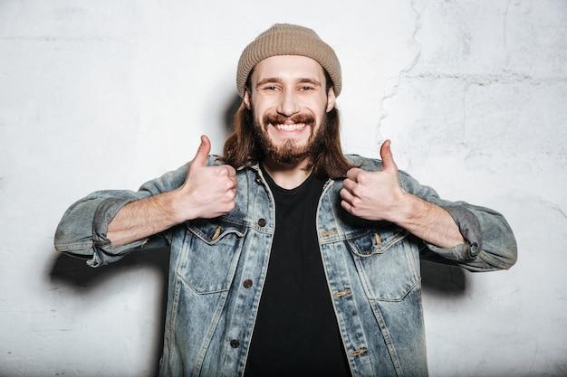 ジーンズのジャケットを着た帽子をかぶった若い幸せなひげを生やしたヒップスターの男は、親指を立てるジェスチャーで壁を越えてポーズをとる
