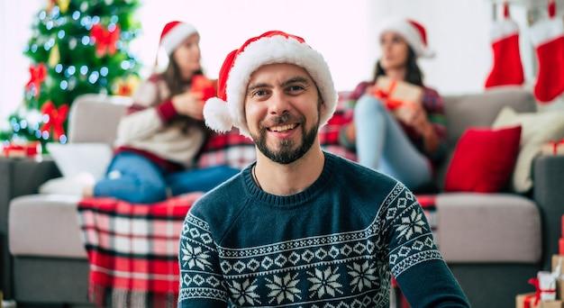 クリスマスのサンタの帽子をかぶった若い幸せなひげを生やした男