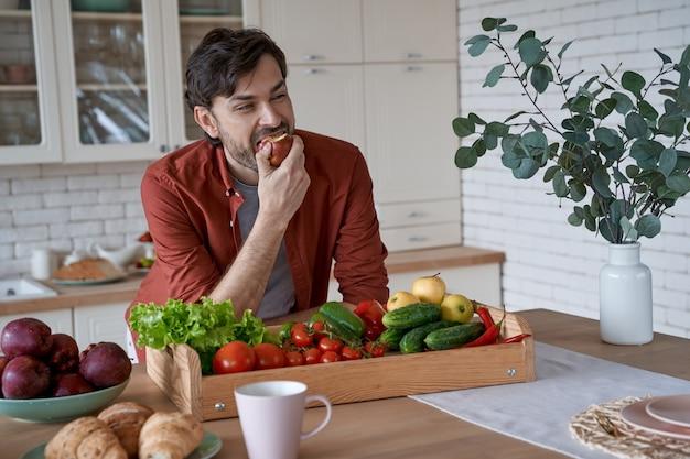 赤いリンゴを食べて、現代に立って笑っているカジュアルな服を着た若い幸せなひげを生やした男