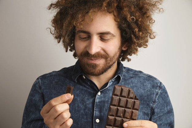 건강한 피부와 곱슬 머리를 가진 젊은 행복한 수염 난 남자가 갓 구운 유기농 초콜릿 바의 맛을 기쁘게 생각합니다.