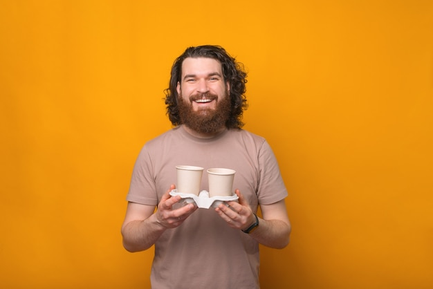 黄色の上に2杯のコーヒーを保持している長い髪の若い幸せなひげを生やした男
