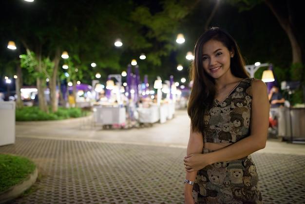 Молодая счастливая красивая азиатская женщина улыбается против живописного вида