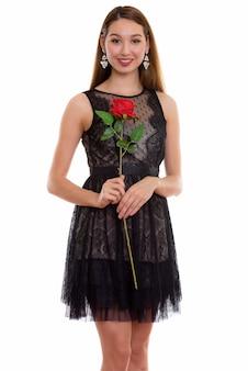 笑顔と赤いバラを押しながら立っている若い幸せな美しいアジアの女性