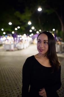 Молодая счастливая красивая азиатская женщина улыбается и думает