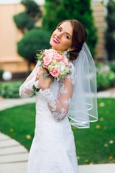 Молодая счастливая красивая невеста в белом элегантном свадебном платье с букетом позирует на открытом воздухе в парке.