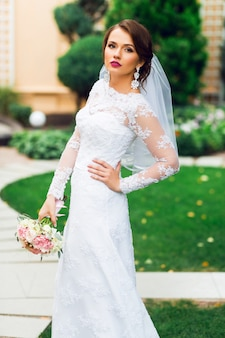 Young happy beautiful bride in white elegant wedding dress with bouquet posing outdoor in park.