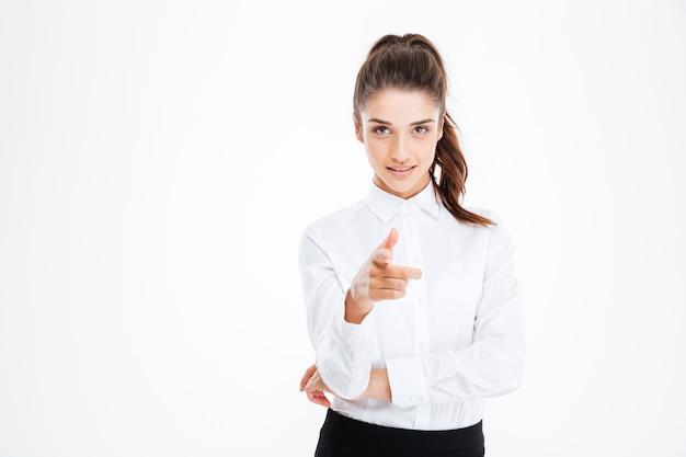 Молодая счастливая красивая деловая женщина, указывая на фронт, изолированную на белой стене